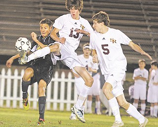 Jonah Wilson (13) and Andrew O'Leary (5) of South Range battle Garfield's Ante Dejanovic (14) for control of the ball in the first half of a Division III district semifinal Tuesday night. Garfield won, 1-0, and will meet Crestview in a district final Saturday.