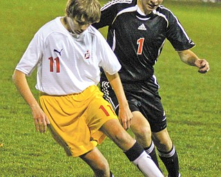 Cardinal Mooney's Nick Tkacik (11) keeps the ball away from Salem's Seth Brine (1) during the first half of their Division II district semifinal Wednesday at the Valley Sports complex in Struthers. The Cardinals downed the Quakers, 5-2, to advance the district final against the Lakeview Bulldogs on Saturday. The Bulldogs defeated Canfield on Wednesday during the semifinal at Cortland.
