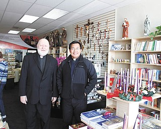 The Rev. Jeffrey Mickler, left, superior of the Society of St. Paul in Ellsworth, and the Rev. Tony Bautista, director of St. Paul's Books and Gifts, are shown in the store that opened in August. Below, the store in Boardman is in a convenient location for 