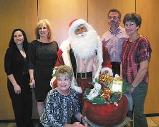 Promoting the holiday open house planned Friday, Saturday and Nov. 4 at D.D. and Velma Davis Education & Visitor Center at Fellows Riverside Gardens in Mill Creek MetroParks are Eileen Stankovich, foreground, and from left, April Stanislaw, Jeanne Simeone, the life-size Santa Claus to be raffled, Keith Kaiser and Janet Yaniglos.