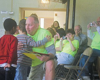 Bill Sheldon, an Austintown schools custodian for 18 years, hugs Lynn Kirk Elementary students who created songs, books and poems for him. Sheldon, who was diagnosed with lymphoma in August, is undergoing chemotherapy and will start working at Fitch High because of a lowered immune system.