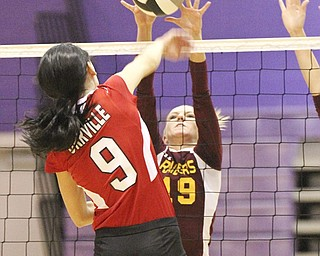 South Range middle hitter Caitlyn Adams (19) blocks a shot by Orville's Rylee Scott (9) during the Division III regional volleyball semifinal Thursday at Barberton High School. The Raiders fell to the Red Riders, 3-1.