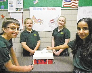 Holy Family School, Poland, conducted a mock presidential debate and election. The tradition began in 1988. Students in third through eighth grades were eligible to vote. Shown are Michael Puhalla, grade 7, casting his vote; Kieran Burke, grade 8; Ellie McDanel, grade 8; and Michelle Hanna, grade 7, placing her ballot in the box. When the votes were counted, Mitt Romney received 62 percent of the votes while Barack Obama received 38 percent.