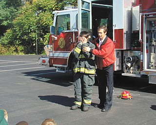 Members of the Eagle Joint Fire District of Hubbard visited St. Patrick School in Hubbard, where firefighters explained the importance of fire safety and demonstrated what to do in case of a fire at home or at school. Students toured the fire trucks and had the opportunity to spray water from a fire hose. Seventh-grader Julian Maiorano dressed in the turn-out gear that a firefighter would wear to a fire call. He is shown with Captain John Petro, Hubbard Fire Department.