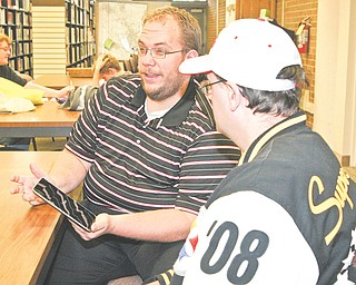 George Garrett, left, demonstrates new technology to Greg Stevens at the Girard library. Local libraries are taking advantage of new technology to make information accessible to the public.