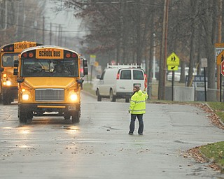 An Austintown schools crossing guard stops traffic on Idaho Road at Woodhurst Drive on Monday. Last week, Darcy Fletcher, another crossing guard, was struck by a vehicle on Idaho. She suffered a fractured skull and remains hospitalized.