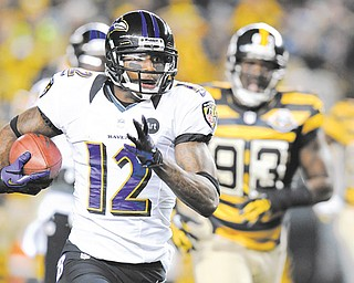Baltimore Ravens' Jacoby Jones (12) returns a punt past Pittsburgh Steelers Jason Worilds (93) on his way to a touchdown in the first quarter of an NFL football game on Sunday in Pittsburgh.