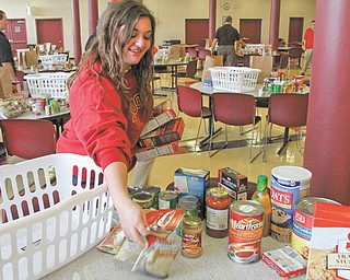 Monica Mattiussi of Cardinal Mooney High School helps to sort food items to be distributed to the needy. Students packed the baskets after school Monday, and juniors and seniors will deliver the baskets to Catholic Charities today for distribution to families.