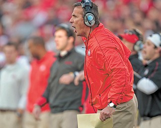Ohio State coach Urban Meyer directs his team from the sidelines during the first half of a game against Wisconsin on Saturday in Madison, Wis. Ohio State won 21-14 in overtime.