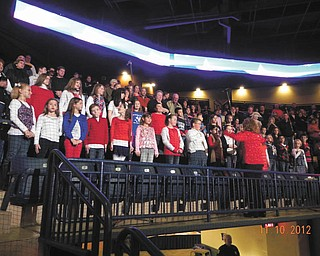 "Members of Holy Family Parish Youth Choir, directed by Barbara Zorn, recently performed patriotic songs in honor of Veterans Day at the Phantoms Hockey game at the Covelli Center, Youngstown. About 30 third- through 12th-graders sang the National Anthem and a medley of U.S. service songs to honor the Army, Navy, Marines, Air Force and Coast Guard. They ended with ""God Bless America."" The choir is composed of students from Holy Family School in Poland with surrounding public schools districts and Cardinal Mooney High School."