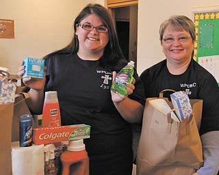 Elizabeth Ruminski, 16, left, and Pastor Carla Davies hold items from the Non-Food Pantry at the Woodland Park United Methodist Church in McDonald.