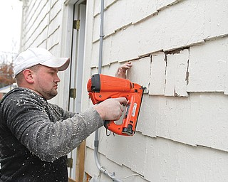 Mike Sackela replaces siding after blowing insulation into a wall during renovations at 867 Lanterman Ave., the