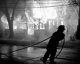 Youngstown fire fighters attempt to put out the massive fire of a vacant house located off Market Street in Youngstown.