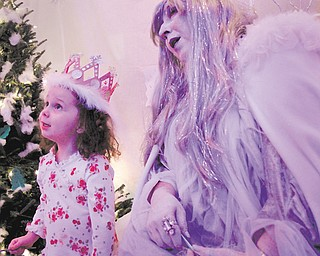 Norah Baker, 3, of Hubbard, makes a wish for snow with Snow Queen Barbara Root during Winter Nights on Sunday at Mill Creek MetroParks' Fellows Riverside Gardens.