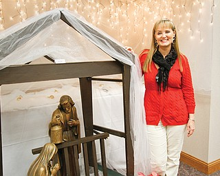 Julie Arena, marketing director at the Villa Maria Community Center, poses with the largest Nativity scene on display, which is used every year by the Sisters in Magnificat Chapel.