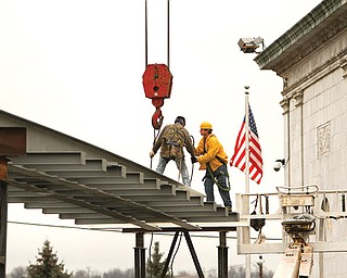 Ironworkers Local 207 members John Gallagher of Youngstown, left, and Tim Evans of Boardman, working for Diamond Steel of Boardman, assemble a new walkway between the Butler Institute of American Art and Butler North. The bridge will be a walkway gallery and will display the museum's historic glass-bell collection.