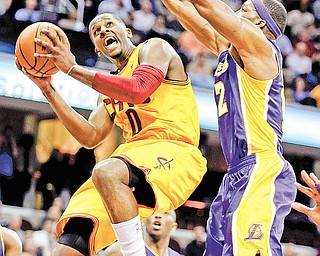 Cleveland Cavaliers' C.J. Miles, left, goes in for a shot against Los Angeles Lakers' Dwight Howard in the second quarter of a game Tuesday in Cleveland.