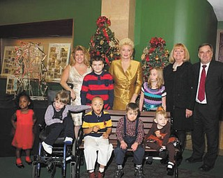 "GFWC Ohio Warren Junior Women's League celebrated its 43rd annual Champagne Luncheon, ""An Officer and a Gentleman Christmas,"" Nov. 16 at Packard Music Hall in Warren. Proceeds went to the Children's Rehabilitation Center so no child will be turned away because of inability to pay for physical, developmental or speech therapy. Some of those who enjoyed the festivities were, front, Faith Rodgers, left, Johnathon Brown, Damon Reed, Justin Keener and Giuilianna Villio. Standing are Karen Margala, WJWL president; John Blake; Julie Vugrinovich, luncheon chairwoman; Katlyn Welch; Esther Garland, fashion coordinator; and Bob Foster, executive director of CRC. Children who attend the center modeled winter outfits during the fashion show and were given the clothes."