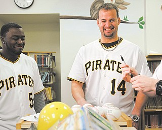 "Pittsburgh Pirates players Josh Harrison, Gaby Sanchez and Alex Presley sign baseballs Wednesday at Poland Union Elementary School. The players, along with manager Clint Hurdle, later played ""We-Are-Family"" Feud with students in the school's gymnasium."