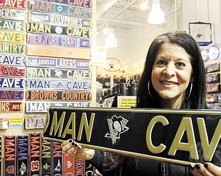 "Touchdown Gifts owner Stephanie Mansour holds a Pittsburgh Penguins ""Man Cave"" sign in her store in Boardman's Southern Park Mall. Hockey merchandise sales are way down because of the lockout."