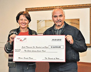 Amy Davidson, left, of Silver Lining Cancer Fund, is shown with Rich Cancio, a member of Friends of Hope, who presented her with an oversized check for $8,650 that was earned at a benefit at Our Lady of Mount Carmel Church in Youngstown in October by the Friends of Hope. The Silver Lining Cancer Fund helps provide wigs, cab fare and grocery items to those who are in active cancer treatment. Cancio's wife, Bebe is a cancer survivor.