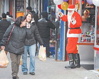 Albert Rodriguez smiles and waves as he tries to lure last-minute holiday shoppers into a store Monday