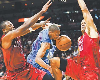 The Oklahoma City Thunder's Russell Westbrook (0) is blocked by the Miami Heat's Dwyane Wade (3) and Shane