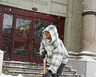 MADELYN P. HASTINGS | THE VINDICATOR..Al Davis, employee of the Youngstown Metropolitan Housing Authority shovels the walkway outside of the building during the first big snow storm of the year. .. - -30-..