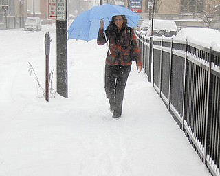 MADELYN P. HASTINGS | THE VINDICATOR..Jennifer Pence shields herself with an umbrella for her walk from City Hall in downtown Youngstown during the first big snow storm of the year. .. - -30-..
