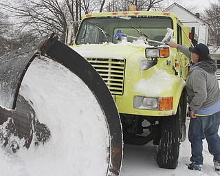 William D LEwis The vindicator  Youngstown city plow driver Mark Poklemba stopped near South ave to clear snow form his windshild while on his rounds Wed afternoon.