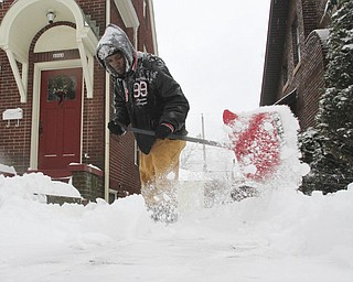 William D Lewis The Vindicator Roberto  Yates of Youngstown clears a driveway on Euclid in Bordman Wed. He and many other were4 out trying to make some cash clearing snow.