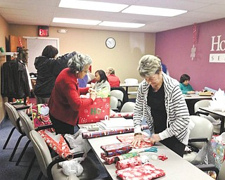 Home Instead Senior Care Caregivers Ann Davis, left, and Barb Costello, with other volunteers, wrap presents Dec. 13 intended for delivery to area senior citizens in the Be a Santa to a Senior event. The Austintown Home Instead Senior Care office has partnered with retailers and community organizations to make sure isolated seniors receive gifts and companionship this holiday season. For information on the Be a Santa to a Senior program visit www.beasantatoasenior.com or call 330-729-1233.