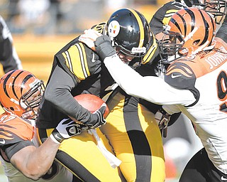 Pittsburgh Steelers quarterback Ben Roethlisberger (7) is sacked by Cincinnati Bengals defensive tackle Geno Atkins (97) and defensive end Michael Johnson (93) in Sunday's loss in Pittsburgh. The Steelers failed to make the playoff s for only the fourth time since 2001, and Roethlisberger says the team's collapse has to do with him not playing well enough down the stretch.