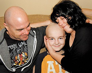 Ty Cook, 14, and his parents, Shawn and Angela, relax at home. Ty, who had a brain tumor removed in September, is feeling better and resting in preparation for nine months of chemotherapy.