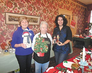 Darlene Bennett, left, Sue Stoddart and Susan Papas hold some of the garage sale items that helped raise money for the Upton House in downtown Warren. The Upton Association also sponsors the Women's Park, the location of a new monument that honors all women. The park is in Warren's historic district between Kinsman House and City Hall. Bricks are available for purchase at www.uptonhouse.org. There also is a mailbox in the park that holds order forms. Upton House is available for rental and guides offer tours.