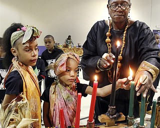 William D Lewis the Vindicator Lynnette Kimako Miller, right, watches as sisters Mercedes , 8, left, and Aniaya Dykes light candles during Kwanzaa celebration Tuesday at McGuffey Centre. Miller was one of the coodinators of the event.