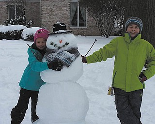 Marissa and Mario Antonelli, 8 and 10, respectively, grandchildren of Ron and Bridget Antonelli of Liberty Township, are enjoying the winter snowstorm during their recent holiday visit here with their parents, Tammy and R.J. Antonelli, from Raleigh, N.C. They made a great snowman with acorn eyes, a carrot nose and broccoli sprouts for its mouth. The snow was a real treat for everyone..
