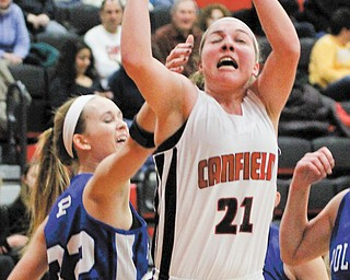 Canfield's Rachel Tinkey (21) goes up for a layup as she is defended by Poland's Kasie Serich (32) during the  first quarter of their All-American Conference American Division basketball game Thursday at Canfield High School. The Cardinals routed the Bulldogs, 56-18.