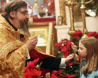 William D Leewis The Vindicator  Sofija Drobnjak, 6, of Hudson kisses a cross held by Rev Milan Medakovic  during Christmas eve service Sunday 1-7-12 at Holy Trinity Serbian Orthodox Church in Youngstown.