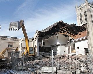Crews began tearing down Pilgrim Collegiate Church on the Youngstown State University campus Tuesday. The area will be used, at least initially, for green space — opening up the view to Jones Hall, the original building on campus.
