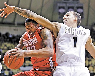 Ohio State guard Lenzelle Smith Jr., left, grabs a rebound under Purdue guard Anthony Johnson in the first half of a game in West Lafayette, Ind., on Tuesday.