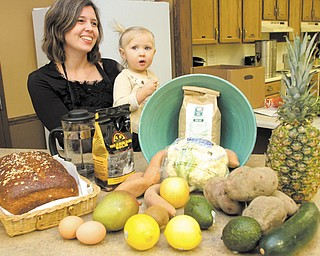 Kathryn Hatch, a member of Glenwood Christian Fellowship in Boardman and promoter of its cafe, Sounds and Grounds, talks about the benefits of organic foods. She's holding her 19-month-old daughter, Talia Pearl. The cafe will be the site of a fundraiser Saturday for Goodness Grows.