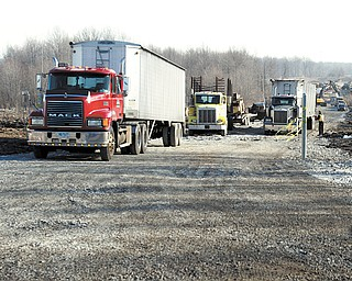 Trucks move in on the unbuilt part of Lanterman Road in Austintown that will be renamed once the Hollywood Slots at Mahoning Valley Race Course is built.