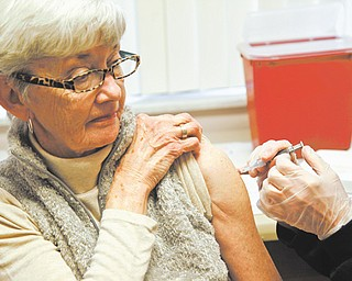 Jeanie Price of Austintown got her influenza shot Thursday at the Mahoning County health department on Westchester Drive, Austintown. Nurses administered about 350 doses of vaccine during clinics Tuesday , Wednesday and Thursday.