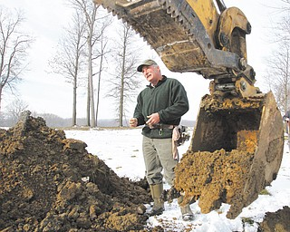 Stephen Prebonick, a state soil scientist, analyzes soil to determine whether a proposed pond site has characteristics that will allow a pond to hold water.