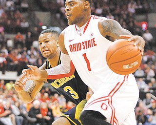 Ohio State's DeShaun Thomas (1) drives down the court as Michigan's Trey Burke (3) tries to keep up during Sunday's NCAA basketball game in Columbus. Thomas posted 20 points for the No. 15 Buckeyes, who handed the No. 2 Wolverines their first loss with a 56-53 win.