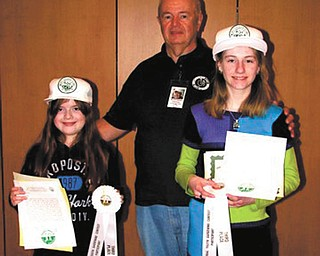 The Men's Garden Club of Youngstown recently honored two members of its Youth Gardening Program. Dave Causer, program coordinator, presented certificates to 9-year-old Greta Graffius, left, and Katelynne, McHugh, 12, for their third place finishes in the national sunflower growing contest. Each of the girls grew a sunflower head measuring 14 inches. For information about the youth program call Causer at 330-548-3669.