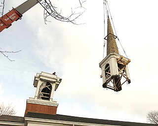 Slow and steady is the pace as parts of the steeple, the spire and lantern are moved by a crane from the roof of First Unitarian Universalist Church, 1105 Elm St., Youngstown, to the ground Tuesday. The spire will be stored, but the lantern and louvre, the wooden structure remaining on the church roof, will be demolished because they are beyond repair.