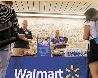Wal-Mart employees Jon Christians and Lori Harris take job applications and answer questions during a job fair at the University of Illinois Springfield campus in Springfield, Ill. Wal-Mart Stores Inc., the world's largest retailer and nation's largest private employer, said Tuesday it is making a pledge to boost its sourcing from domestic suppliers and hire more than 100,000 veterans.
