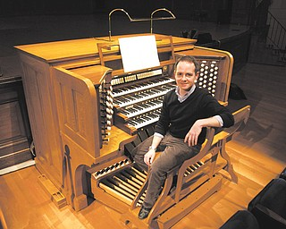 Colin Lynch sits at the console of the pipe organ at Stambaugh Auditorium. Lynch, of Boston, came to